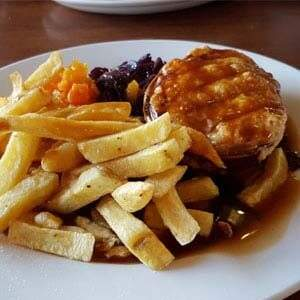 Steak pie served with chips and vegetables